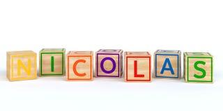 Cubes en bois d'isolement en jouet avec des lettres avec le nom Nicolas Photos stock