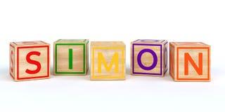 Cubes en bois d'isolement en jouet avec des lettres avec le nom Simon Photographie stock