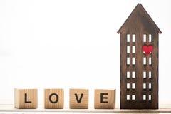 Cubes en bois en bloc avec le signe d'amour et maison en bois Photographie stock