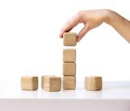 Cubes en bois en pile La main établit la tour de bloc d'isolement Images libres de droits