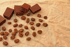 Cubes en chocolat avec les grains de caf? colombiens sur un fond de toile de texture photographie stock libre de droits