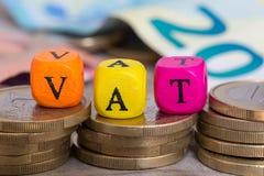 Cubes en lettre de TVA sur le concept de pièces de monnaie images stock