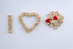 Cubes en sucre disposés comme j'aime le concept de sucre Images libres de droits