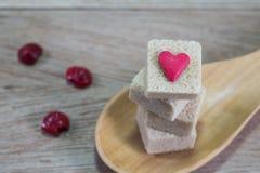 Cubes en sucre roux dans la cuillère en bois sur le fond en bois Photographie stock libre de droits