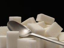 Cubes et cuillère à café en sucre Photo stock