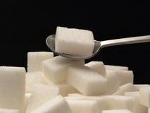 Cubes et cuillère à café en sucre Photographie stock libre de droits