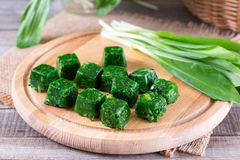 Cubes of frozen spinach. On a wooden cutting board stock photo