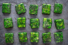 Cubes of frozen spinach on the stone table top view Stock Photography