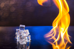 Cubes of ice and fire on a water surface on an abstract backgrou. Nd Royalty Free Stock Image