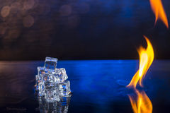 Cubes of ice and fire on a water surface on an abstract backgrou. Nd Royalty Free Stock Images