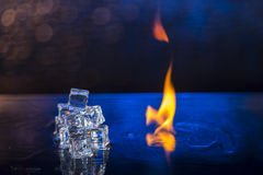 Cubes of ice and fire on a water surface on an abstract background.  Royalty Free Stock Images