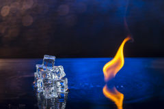 Cubes of ice and fire on a water surface on an abstract background.  Royalty Free Stock Photo