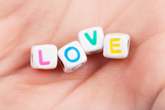 Cubes with love word. Photo of game cubes with love word on woman's palm, romantic holiday, affection symbol, romance relationship, colorful letters in the man's Royalty Free Stock Photography