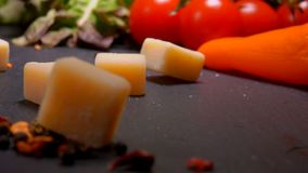 Cubes of Parmesan cheese fall to the surface of the table. Cubes of Parmesan cheese fall to the black surface of the table on the background of greenery and