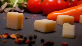 Cubes of Parmesan cheese fall to the surface of the table. On the background of greenery and vegetables stock video