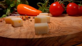 Cubes of Parmesan cheese fall to the wooden board. On the background of greenery and vegetables stock video footage