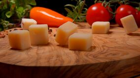 Cubes of parmesan cheese fall to the wooden board. On the background of greenery and vegetables stock footage