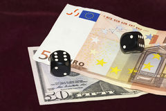 Cubes for poker and pieces of banknotes and fifty dollars and fi. On a red cloth of visible part of the fifty dollar bills and fifty euros. On the bills are Royalty Free Stock Images