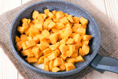 Cubes of pumpkin in a frying pan Royalty Free Stock Photography