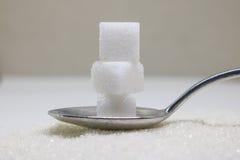 Cubes purs en sucre raffiné et en sucre sur la cuillère Ingredie doux de nourriture image libre de droits