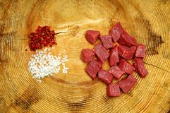 Cubes of raw beef. Raw beef chopped into cubes for a stew on wooden with salt and black pepper Royalty Free Stock Photo