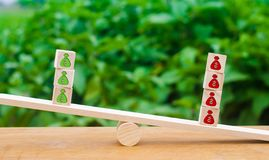 Cubes on scales with red patterns outweigh the money green. The stock photo