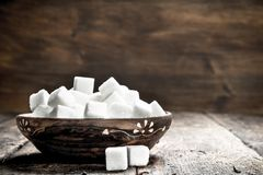 Cubes of sugar in a bowl. On a wooden background royalty free stock photography