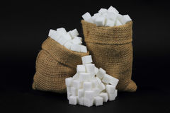 Cubes Sugar in burlap bags over black. Picture of Sugar Cubes in Burlap Bags and spilled on pile  over black Background Stock Photo