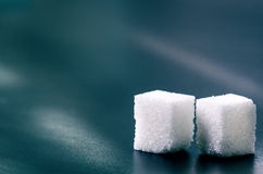 Cubes of sugar on a dark background. Unhealthy ingredients. Lump sugar Stock Images