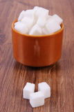 Cubes of sugar in glass bowl on wooden background Stock Photo
