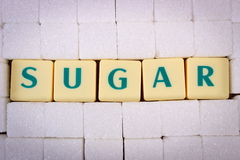 Cubes of sugar and text sugar, ingredient for cooking Royalty Free Stock Images