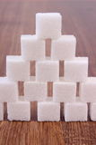 Cubes of sugar on wooden background, ingredient for cooking Royalty Free Stock Photos