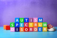 Cubes with text AUTISM SPECTRUM DISORDER. On table Stock Photography