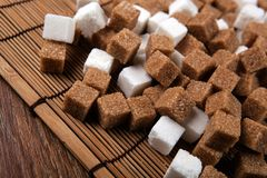 Cubes of white and brown sugar on a bamboo napkin Stock Photo