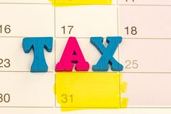 Cubes with word TAX on calenda surface stock images