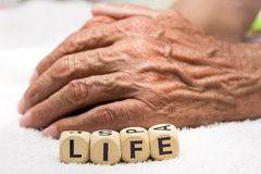 Cubes with the words life on the background of the hands of an e. Lderly person . The concept of retirement Stock Image