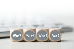 Cubes with the words `who, how, what, when` in front of a keyboard Stock Photo