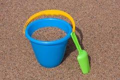Cubeta azul da areia & pá verde na praia Imagem de Stock