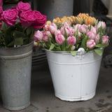 A cubeta branca com um ramalhete de tulipas cor-de-rosa e alaranjadas e de um vaso com rosas vermelhas como uma decoração para a  Imagens de Stock Royalty Free