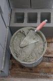 Cubeta com cimento e pá de pedreiro em telhas Foto de Stock Royalty Free