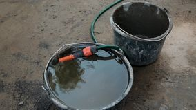 Cubeta completa da água e de uma mangueira no canteiro de obras vídeos de arquivo