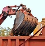 A cubeta da areia de enchimento da máquina escavadora em um corpo do caminhão Imagem de Stock Royalty Free