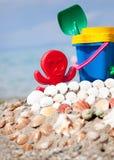 A cubeta da criança, a pá e os outros brinquedos na praia tropical contra b Imagens de Stock