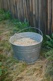 Cubeta da exploração agrícola na grama seca por Cerca Foto de Stock