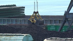 A cubeta da garra descarrega o carvão dos vagões em um cargueiro vídeos de arquivo