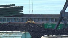 A cubeta da garra do guindaste do porto recolhe o carvão para o transporte filme