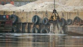A cubeta da garra da máquina escavadora aumenta do rio com espirra da água no porto na perspectiva do filme