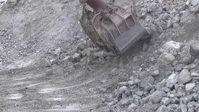 A cubeta da máquina escavadora é enchida com o minério filme