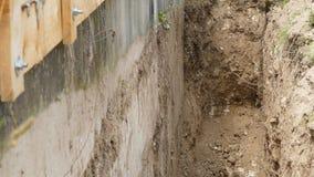 A cubeta da máquina escavadora é submergida em uma trincheira vídeos de arquivo