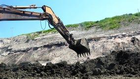 A cubeta da máquina escavadora carrega a argila e os reloads a um outro lugar filme